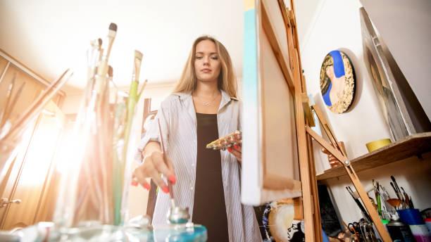 Schöne kaukasische weiße Frau zeichnung das Bild im Inneren. Arbeiten mit Pinsel und Farben. Warme Atmosphäre im Innenbereich. Schönes weiches Licht um – Foto