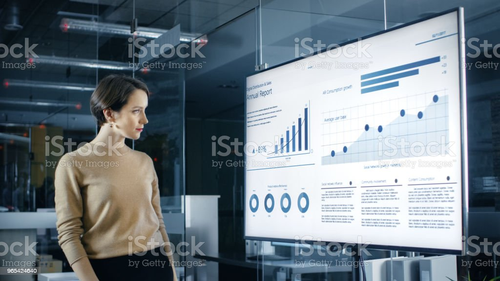 Beautiful Caucasian Woman Analyzes Statistics, Charts and Pies with Company's Growth Shown on a Wall TV. zbiór zdjęć royalty-free
