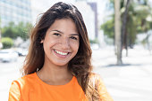 Beautiful caucasian woman in a orange shirt in the citywith buildings and street in the background