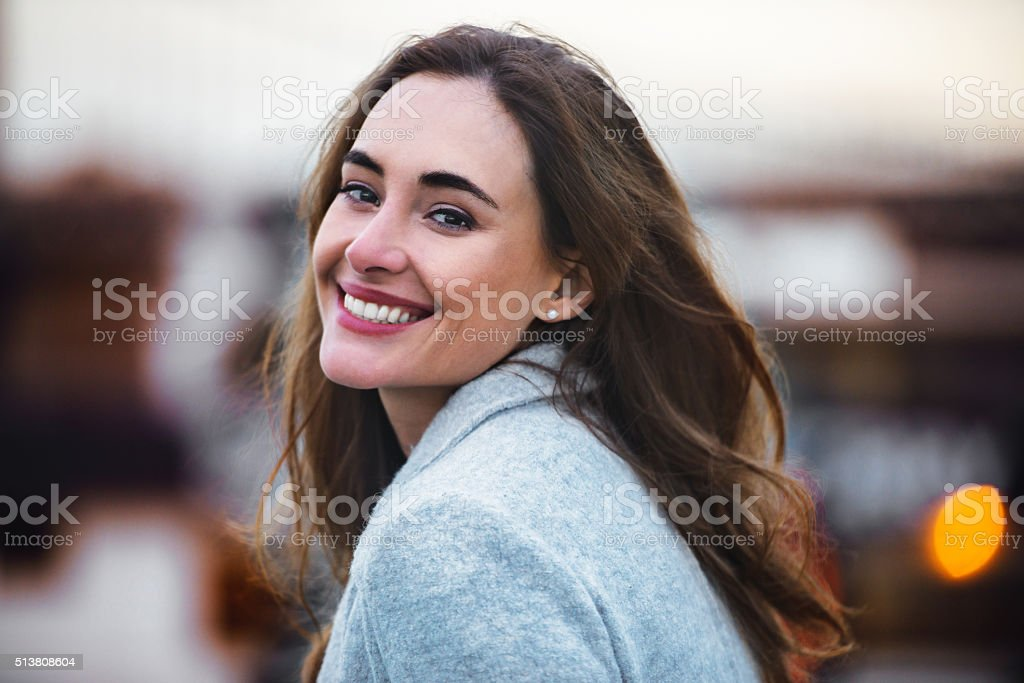 beautiful caucasian woman with charming smile walking outdoors stock photo