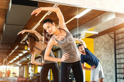511849865istockphoto Beautiful Caucasian woman with ponytail and in sportswear doing side stretching exercises while standing in gym. In background mirror and man in reflection. 1127582489
