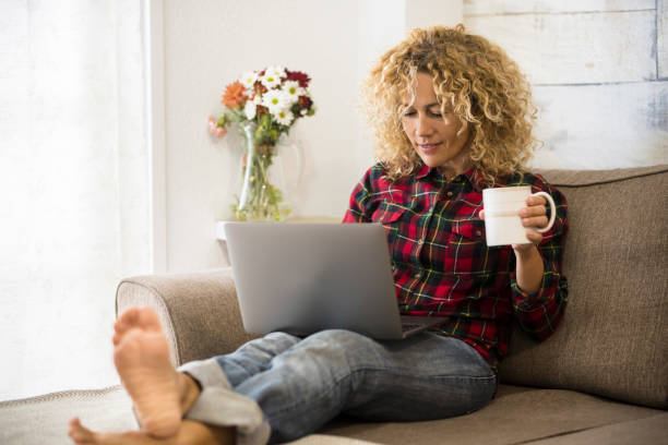 Beautiful caucasian woman work at the laptop computer at home with intenet connection - concept of free job and alternative office - modern people and technology stock photo