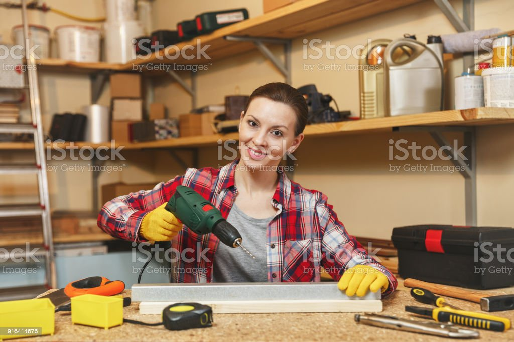 Beautiful caucasian young brown-hair woman in plaid shirt and gray T-shirt working in carpentry workshop at table place, drilling with drill holes in piece of iron and wood while making furniture. stock photo