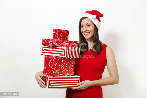 Pretty caucasian young happy woman with charming smile dressed in red dress and Christmas hat holding gift boxes on white background. Santa girl with present isolated. New Year holiday 2018 concept
