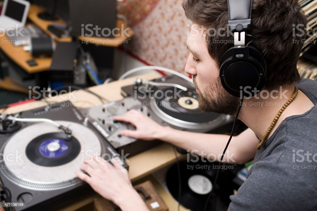 Beautiful Caucasian Young Man DJ Spinning Records in Music Studio stock photo