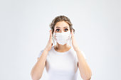 istock Beautiful caucasian young woman in white t-shirt with disposable face mask. Protection versus viruses and infection. Studio portrait, concept with white background. She is gesturing, copy space for your design. She shocked and holds her head 1209098925