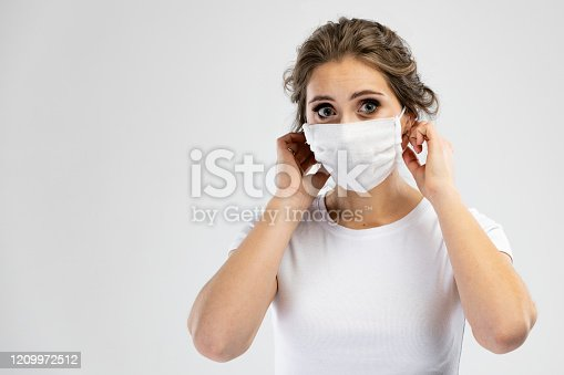 Beautiful caucasian young woman in white t-shirt with disposable face mask. Protection versus viruses and infection. Studio portrait, concept with gray background.