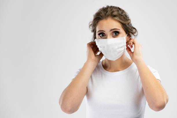 Schöne kaukasische junge Frau in weißen T-shirt mit Einweg-Gesichtsmaske. Schutz vor Viren und Infektionen. Studioportrait, Konzept mit grauem Hintergrund. – Foto