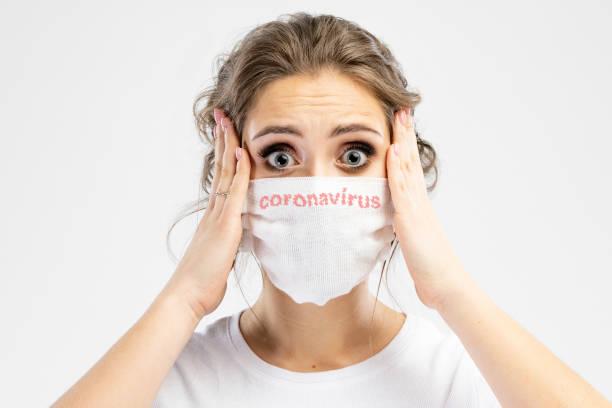 Schöne kaukasische junge Frau in weißen T-shirt mit Einweg-Gesichtsmaske. Schutz vor Viren und Infektionen. Studioportrait, Konzept mit weißem Hintergrund. Sie gestikuliert, kopiert Platz für Ihr Design. Sie schockiert und hält ihren Kopf – Foto