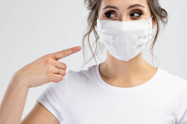 Schöne kaukasische junge Frau in weißen T-shirt mit Einweg-Gesichtsmaske. Schutz vor Viren und Infektionen. Studioportrait, Konzept mit weißem Hintergrund. Sie gestikuliert, kopiert Platz für Ihr Design. – Foto