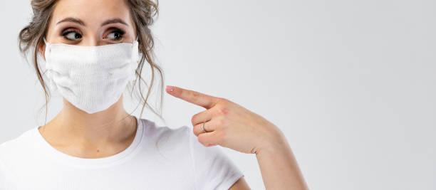Schöne kaukasische junge Frau in weißen T-shirt mit Einweg-Gesichtsmaske. Schutz vor Viren und Infektionen. Sie gestikuliert, kopiert Platz für Ihr Design. – Foto