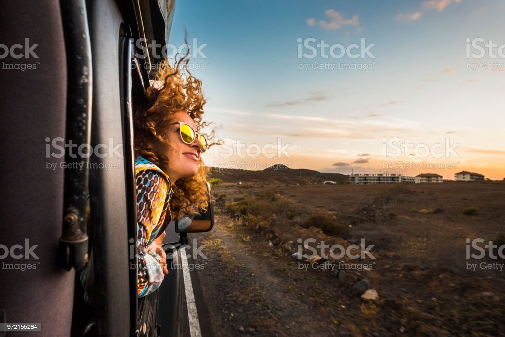 beautiful caucasian young woman travel outside the car with wind in the curly hair, motion and movement on the road discovering new places during a nice sunset, enjoy and joyful freedom concept royalty-free stock photo