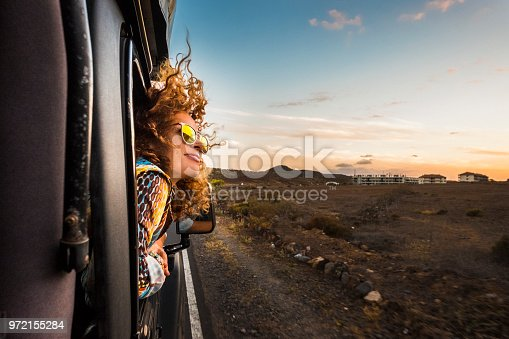 istock beautiful caucasian young woman travel outside the car with wind in the curly hair, motion and movement on the road discovering new places during a nice sunset, enjoy and joyful freedom concept 972155284