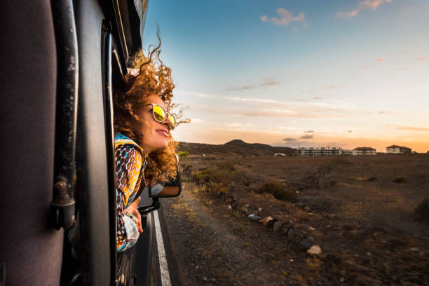 beautiful caucasian young woman travel outside the car with wind in the curly hair, motion and movement on the road discovering new places during a nice sunset, enjoy and joyful freedom concept stock photo