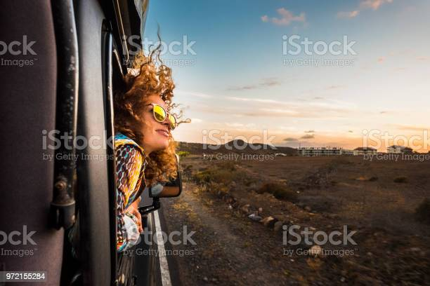 beautiful caucasian young woman travel outside the car with wind in the curly hair, motion and movement on the road discovering new places during a nice sunset, enjoy and joyful freedom concept