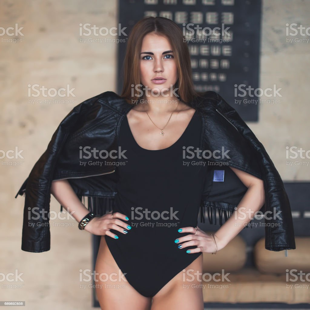 Beautiful Caucasian young woman with blue eyes, pouty lips and long hair wearing bodysuit and leather jacket standing in studio looking at camera stock photo
