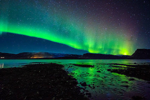 beautiful celestial aurora borealis in iceland's winter sky near waterstream - nightsky bildbanksfoton och bilder