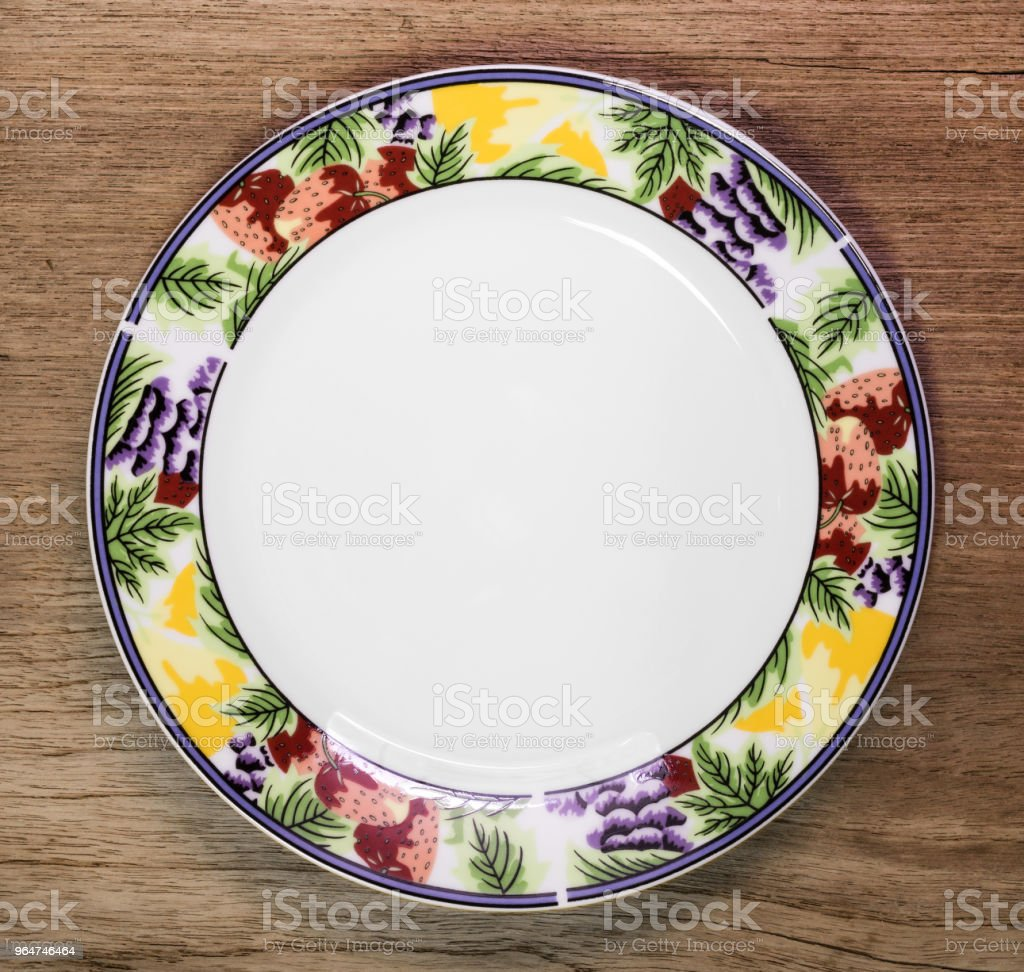 Beautiful ceramic dish on wooden table background. Design plate in fruit pattern style. royalty-free stock photo