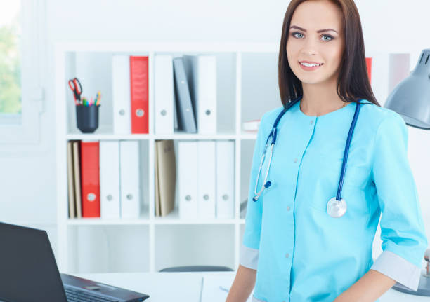 Beautiful charming friendly smiling female medicine therapeutist doctor standing in office. Medical help or insurance concept. stock photo