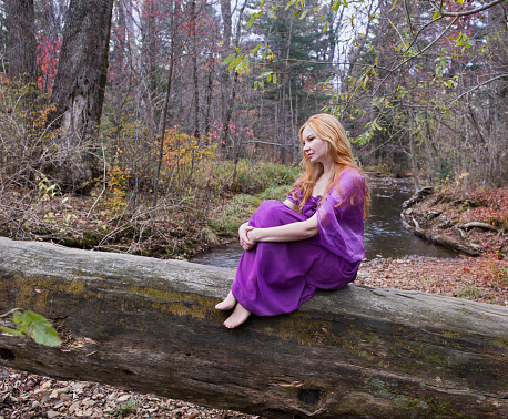Beautiful charming girl sitting on the log in the forest