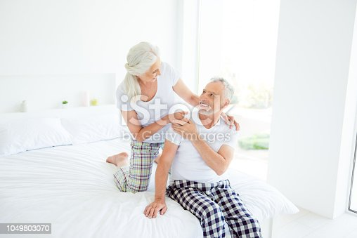 istock Beautiful, charming grey hair grandma put her hand to granddad shoulder, looking into eyes and enjoy sitting on the couch on vacation 1049803070