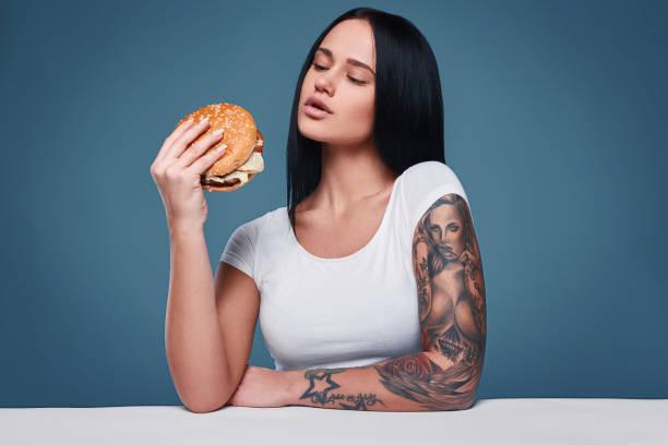 beautiful charming tattoo girl holding hamburger - essen tattoos stock-fotos und bilder