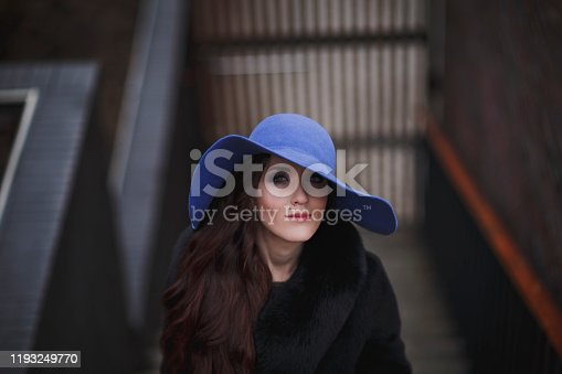 Beautiful charming young woman in a blue hat walks in the park in early spring