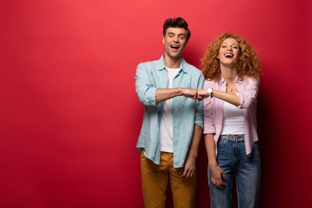 beautiful cheerful couple bumping fists, isolated on red stock photo