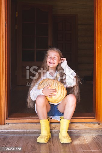 A beautiful cheerful caucasian girl with long blond hair is sitting on the doorstep of the house, holding a large orange pumpkin in her hands. Halloween, Thanksgiving, holiday. Autumn harvest.