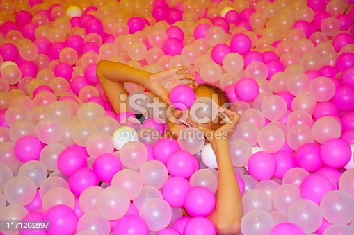 544818734 istock photo Beautiful cheerful girl with pink bright plastic balls. Pool with multi-colored balls. 1171262897
