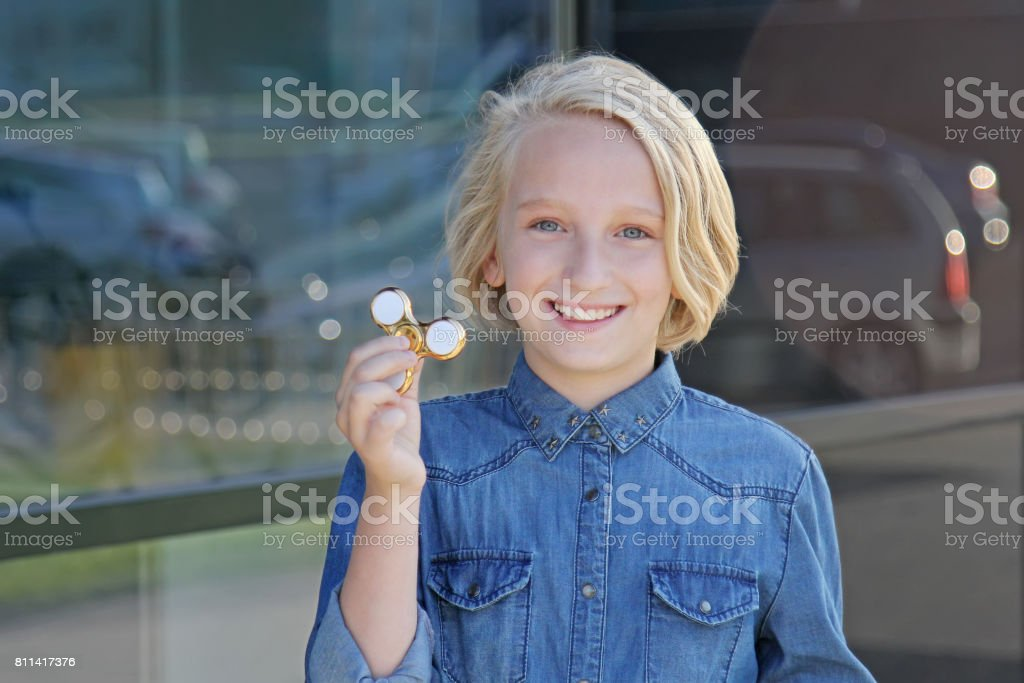 Beautiful cheerful school girl playing with a gold fidget spinner. A popular trendy toy. stock photo