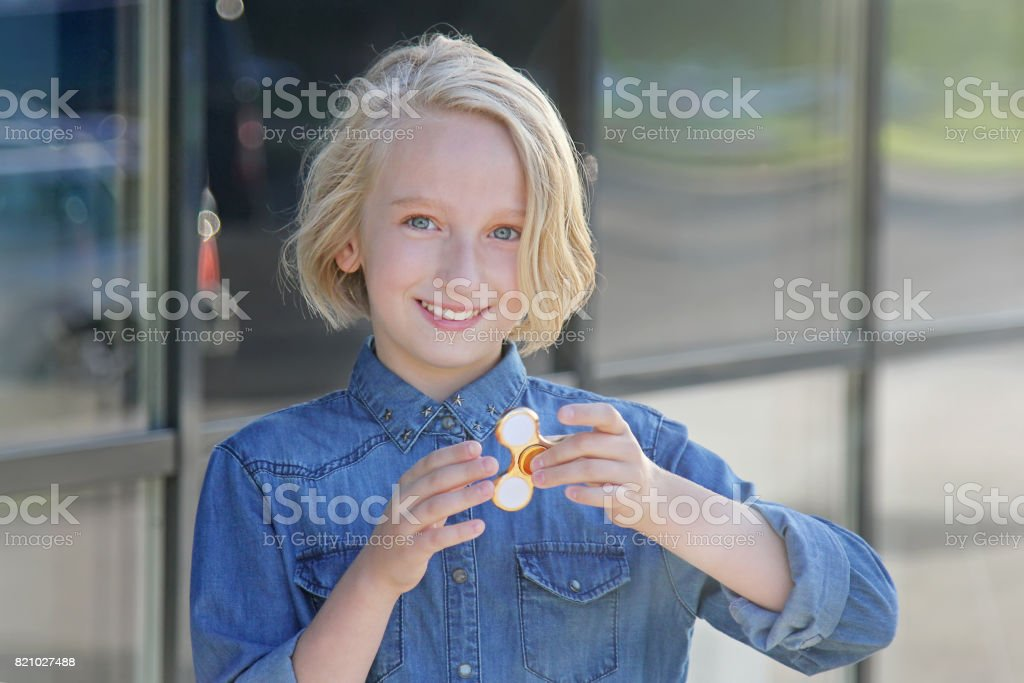 Beautiful cheerful school girl playing with a gold fidget spinner. A popular toy for children and adults. stock photo