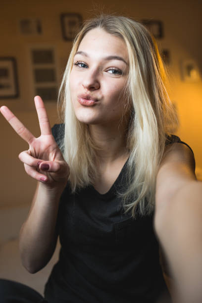Beautiful Cheerful Teenage Girl Taking a Selfie in Bedroom Beautiful Cheerful Teenage Girl Taking a Selfie in Bedroom. puckering stock pictures, royalty-free photos & images