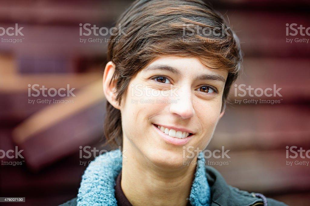 Beautiful cheerful young androgynous British woman smiling stock photo