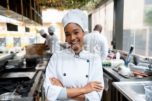 Portrait of a beautiful female chef working in a kitchen at a restaurant and looking at the camera smiling – gastronomy concepts