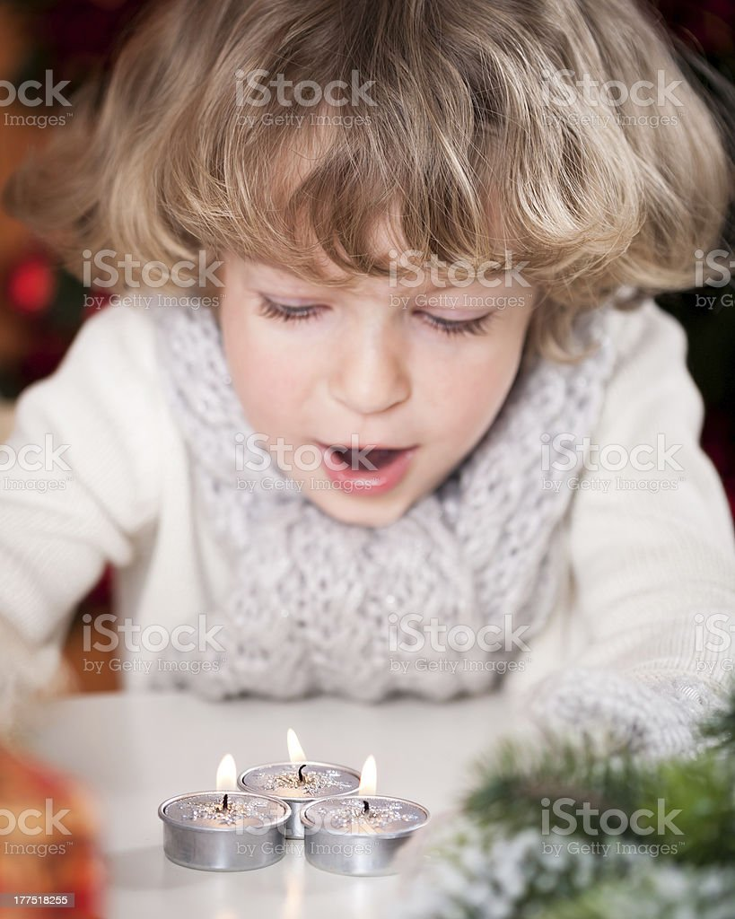 Beautiful child blowing out candles royalty-free stock photo