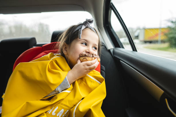 Beautiful child eating a doughnut while looking through a car window stock photo