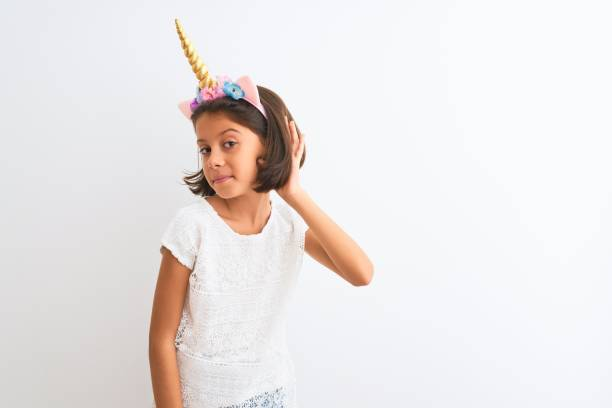 Beautiful child girl wearing unicorn diadem standing over isolated white background smiling with hand over ear listening an hearing to rumor or gossip. Deafness concept. Beautiful child girl wearing unicorn diadem standing over isolated white background smiling with hand over ear listening an hearing to rumor or gossip. Deafness concept. diademe stock pictures, royalty-free photos & images