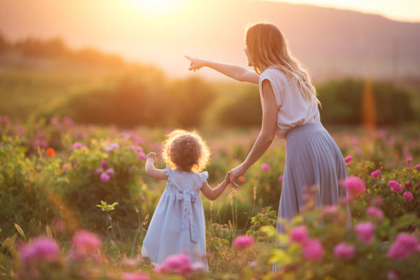 Beautiful child girl with young mother are wearing casual clothes walking in roses garden over sunset lights stock photo