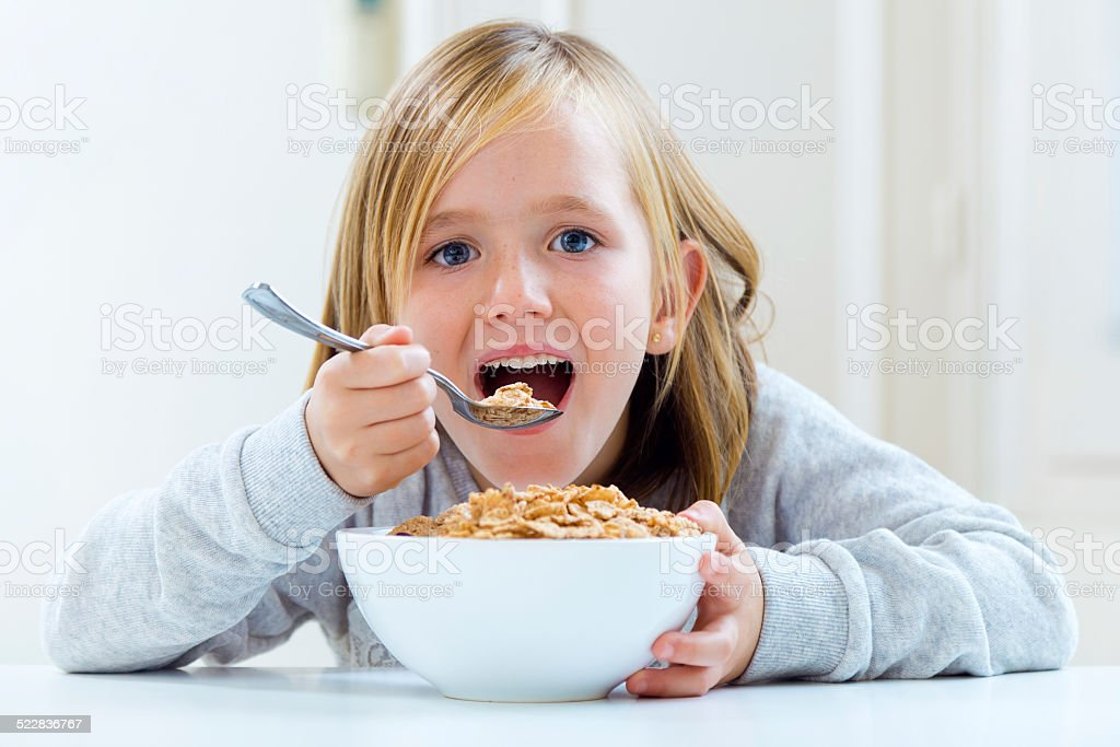 Beautiful child having breakfast at home. stock photo