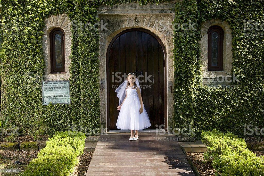 Beautiful child in white dress outside chapel stock photo