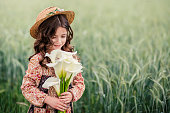 Cute little girl looking at bouquet of flowers in her hands while standing in the fields of wheat