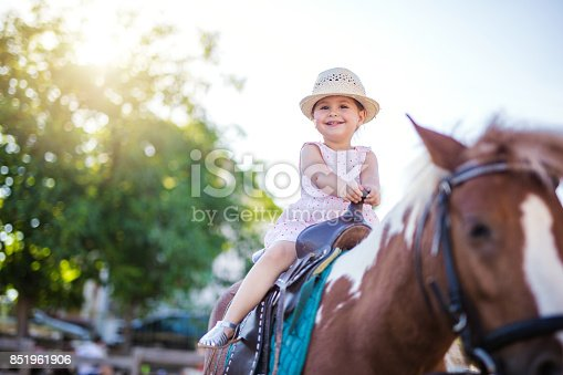 Photography of a 2 years old child on a horseback. This is her first experience on a horse, and she is overwhelmed with various emotions