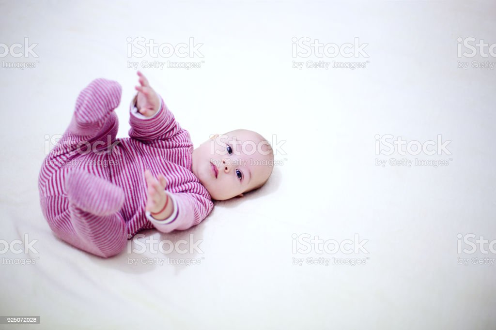 beautiful child playing with his legs on the bed in bedroom. - foto stock