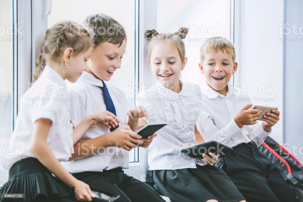 Hermosos hijos son estudiantes en un aula en la escuela reciben educación tabletas feliz - foto de stock