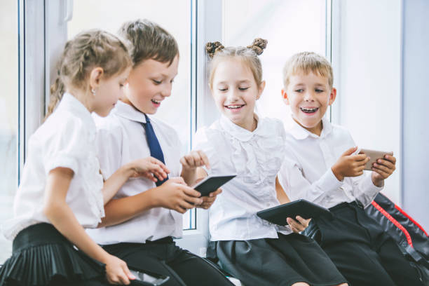 Beautiful children are students together in a classroom at the school receive education with tablets happy stock photo