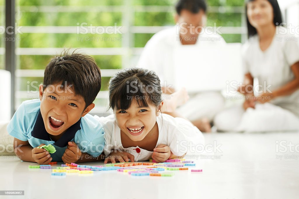 Beautiful children lying on the floor and playing. royalty-free stock photo