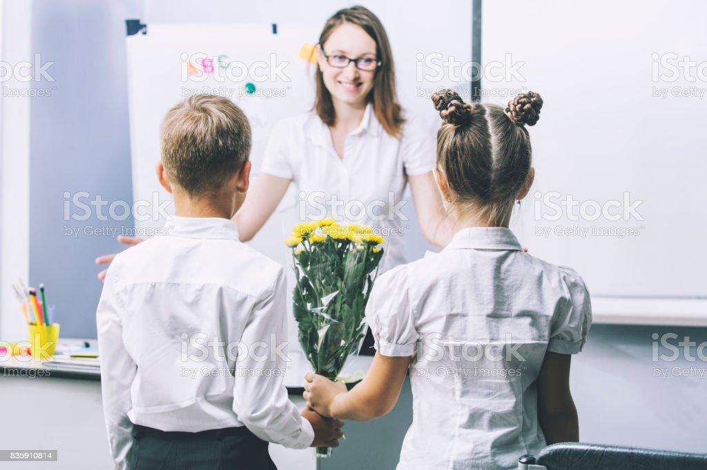 Hermosos niños de escuela con flores para los profesores en la escuela - foto de stock