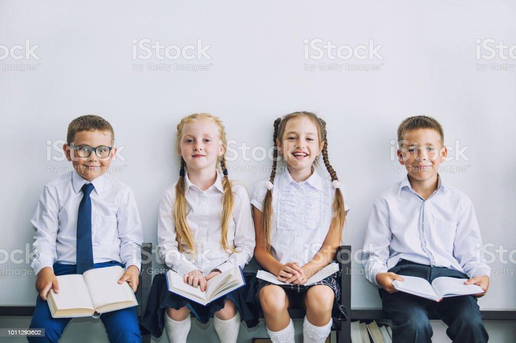 Hermosos hijos con los libros que estudiaron juntos en el aula en la escuela uniforme Haz educados feliz - foto de stock