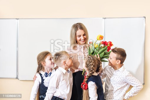 istock Beautiful children-students together in class at school give flowers to their best woman teacher 1153869225